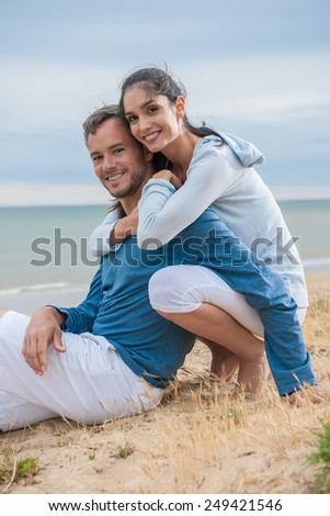 nice couple sitting in the sand in casual clothes, looking at the camera - stock photo