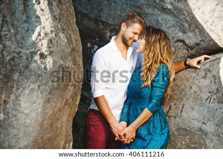 Nice couple standing together very close to each other near rocks, outdoor. Profile. Girl wearing blue dress and man wearing white shirt and claret trousers - stock photo