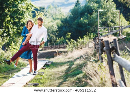 Nice couple walking together, outdoor, in the countryside. Beloved raised right leg. Woman wearing blue dress and light blue shoes and man wearing white shirt, claret trousers and black shoes. - stock photo