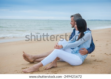 nice couple wearing casual clothes and looking at the ocean - stock photo