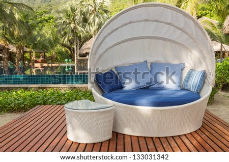 Nice cozy white round chair with canopy and blue cushions - stock photo