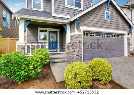 Nice curb appeal of two level house, mocha exterior paint and concrete driveway, trimmed bushes and green lawn - stock photo