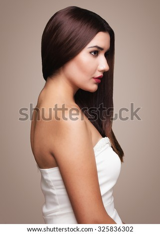 Nice dark Brown haired girl standing, looking left, wearing White dress, hair dresser beauty saloon pose