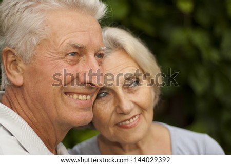 Nice elderly couple in the garden on a background of green trees and bushes