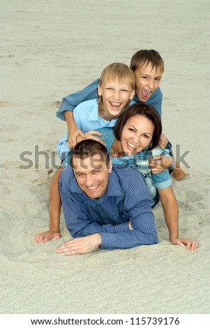 nice family in blue lying on the sand