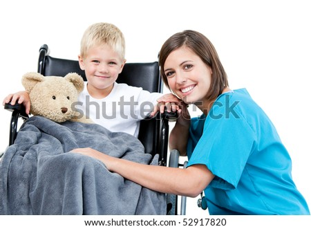 Nice female doctor carrying adorable little boy with his teddy bear in the wheelchair at the hospital - stock photo