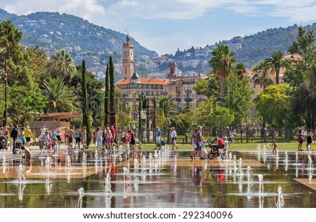 NICE, FRANCE - AUGUST 23, 2014: People among fountains at Promenade du Paillon - 12 hectares, 1.2km long new green pedestrian walkway area in the heart of Nice opened on October 26, 2013. - stock photo