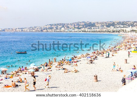 NICE, FRANCE - AUGUST 23, 2012: Tourists enjoy the good weather at the beach in Nice, France. The beach and the waterfront avenue, Promenade des Anglais, are full almost all the year. - stock photo