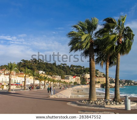 NICE, FRANCE - DECEMBER 05, 2005: People take a walk on winter day at pedestrians on Promenade des Anglais with palm trees in Nice, France on December 05, 2005. 