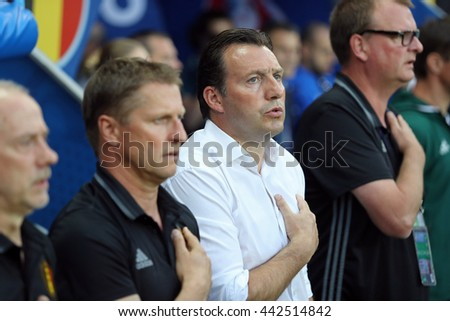 NICE, FRANCE - JUNE 22, 2016: Head Coach of Belgium National football team Marc Wilmots and his assistants sing national anthem during UEFA EURO 2016 game against Sweden at Allianz Riviera stadium - stock photo