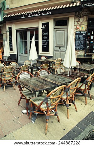 NICE, FRANCE - MAY 14, 2013: Outdoor french traditional cafe with old wood tables and wicker chairs in Old Town of Nice, French Riviera, France - stock photo
