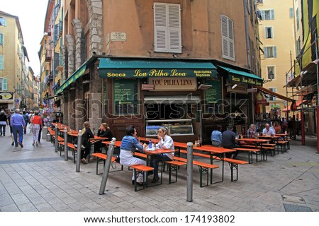 NICE,  FRANCE - MAY 14, 2013: People having lunch at french outdoor cafe in the Old town Nice - the largest resort and tourist town on the French Riviera, Cote d'Azur, France. - stock photo