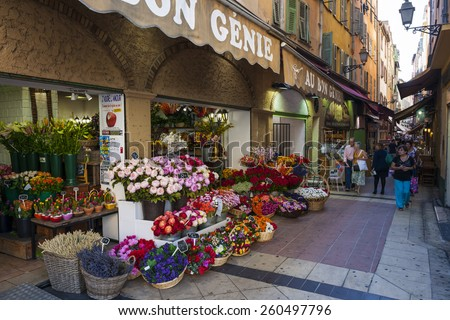 """NICE, FRANCE - OCTOBER 2, 2014: """"Au bon genie"""" flower shop on pedestrian Rue Pairoliere, a quaint shopping street lined with food and souvenir shops. - stock photo"""