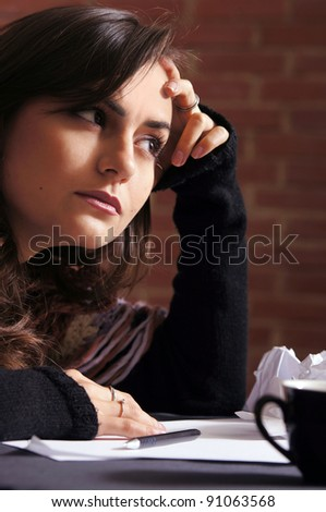 nice girl at table thinking with papers