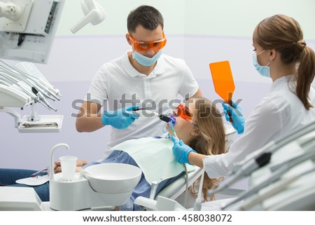 Nice girl in blue shirt, jeans and patient bib on the patient chair in the dental cabinet. Next to her there is a male dentist and a female assistant. They both wear white uniform with blue latex - stock photo