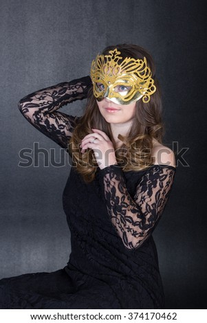 nice girl in mask and black dress - stock photo