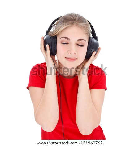 Nice girl in red t-shirt relaxing by listening music with headphones over white background - stock photo
