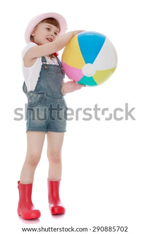 Nice girl in rubber boots and shorts holding a ball - isolated on white background - stock photo