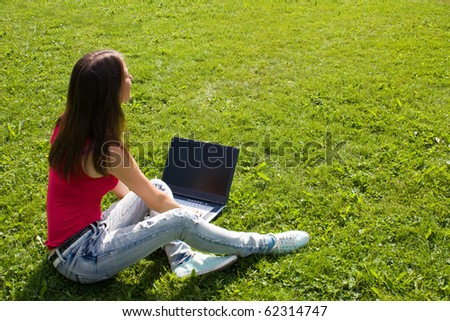 Nice girl looking at laptop monitor in the park