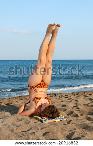 Nice girl making exercises on beach at evening - stock photo