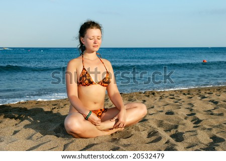 Nice girl meditating on the beach at evening - stock photo