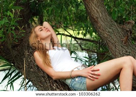 Nice girl sleeping  on the tree - stock photo