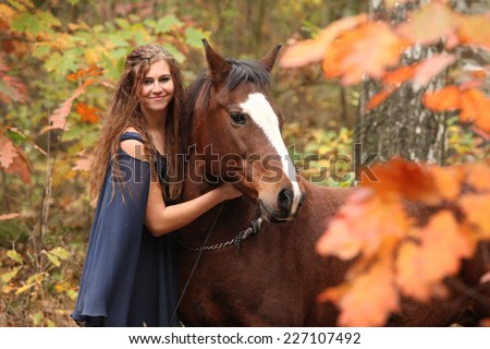 Nice girl together with brown horse in autumn - stock photo