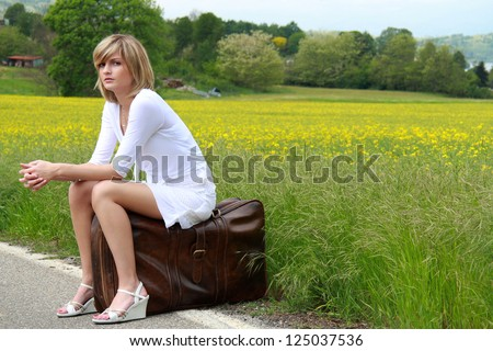 Nice girl white dressed is waiting on a suitcase at the border of the road. Travel conceptual