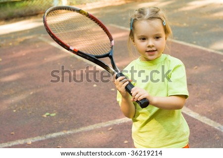Nice girl with racket in hands playing game of tennis - stock photo