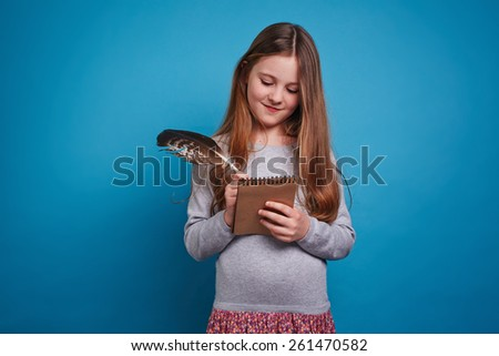 Nice girl writing in her notebook with a feather pen - stock photo