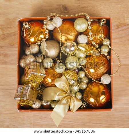 Nice golden christmas balls in a box on wooden surface. - stock photo