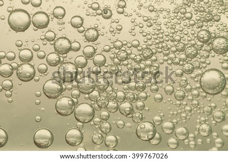 Nice golden fizz bubbles floating toward the surface - stock photo