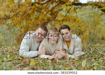 Nice happy family lying in autumn park - stock photo