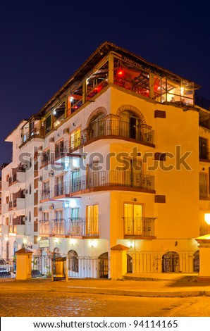 Nice hotel building with roof restaurant at night in Puerto Vallarta, Mexico. - stock photo