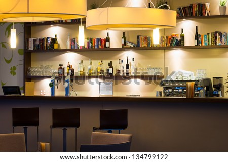 nice hotel lounge bar with bottle shelfs and seats, tables, lights - stock photo