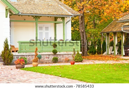 Nice house with garden at autumn - stock photo