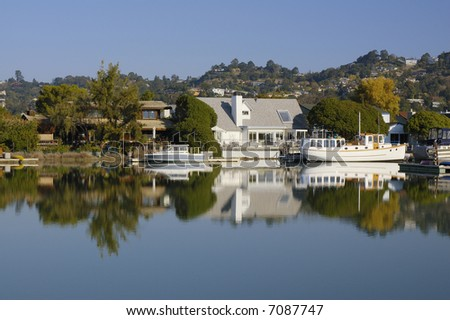Nice houses with boats are reflected in calm waters of Corte Madera Creek in Larkspur, California.