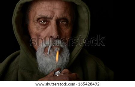 Nice Image of a senior man lighting a marijuana joint - stock photo