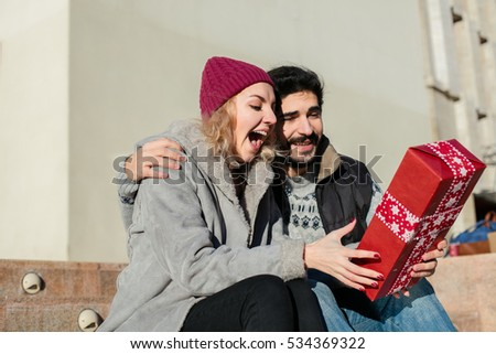 nice joyful couple standing outside on stairs of a building, the boy offering a gift for his girlfriend