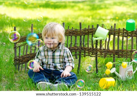 Nice kid in the garden sitting on the green grass by the lath fence surrounded with soap bubbles