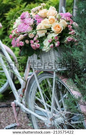 Nice lilac bicycle with pretty twisted basket of colored roses in it standing near the green bush - stock photo