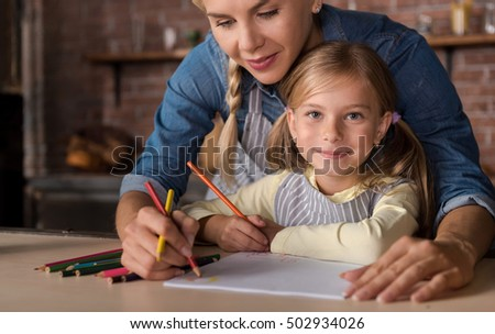 Nice little girl drawing with her mother in the kitchen