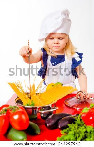Nice little girl in cap cooking pasta - stock photo