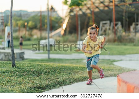 nice little girl is running in the park - stock photo