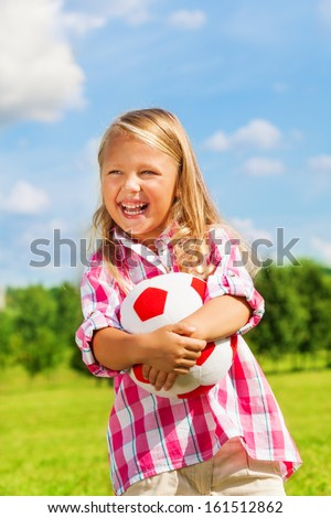 Nice little 6 years old blond cute girl in pink shirt holding soccer ball - stock photo