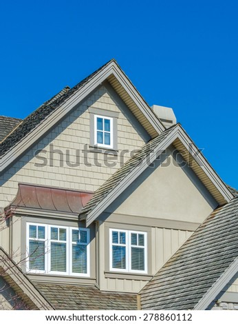Nice looking windows at the roof of the house. - stock photo