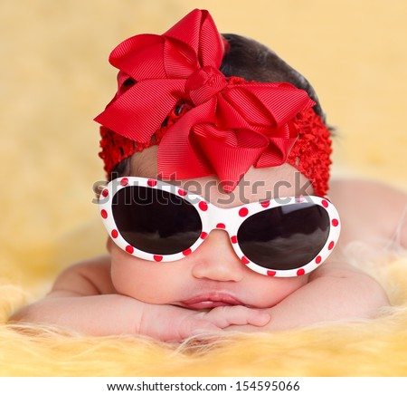 Nice newborn baby girl posing with sunglasses on  yellow fur and white background wearing a red ribbon.