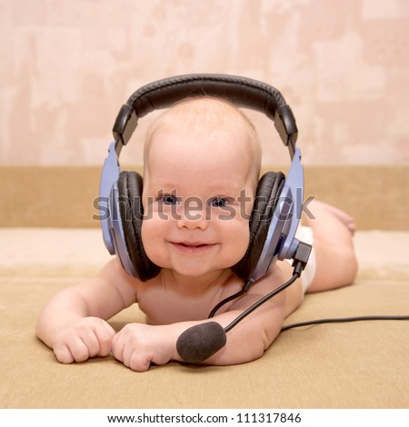 "Nice newborn baby with blue eyes smiling wearing a headset. ""Can I help you?"" Or teaching a foreign language, or listening to a fairy tale. - stock photo"