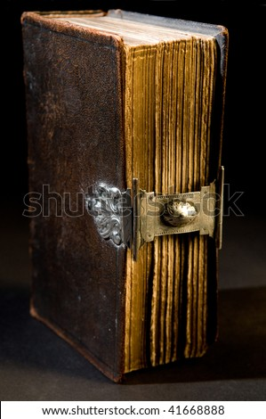 Nice old bible with an old lock on a black background. - stock photo