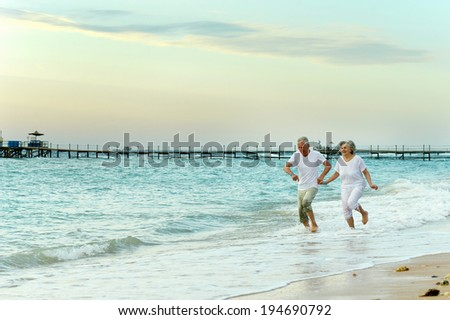Nice old couple running on sea beach - stock photo